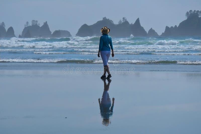 Kvinna som går på stranden med sceniska sikter av havsbuntar arkivfoto