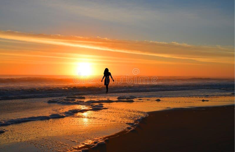 Kvinna som går på stranden på soluppgång royaltyfri foto