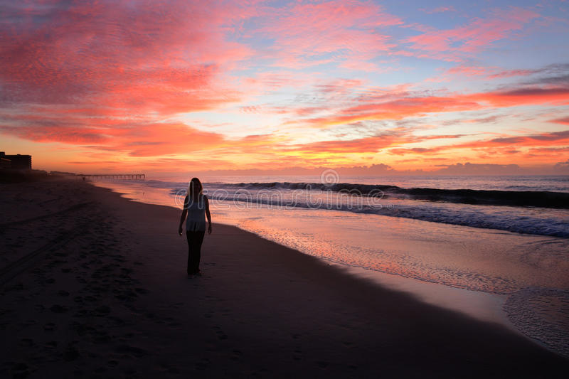 Kvinna som går på stranden på soluppgång royaltyfria bilder