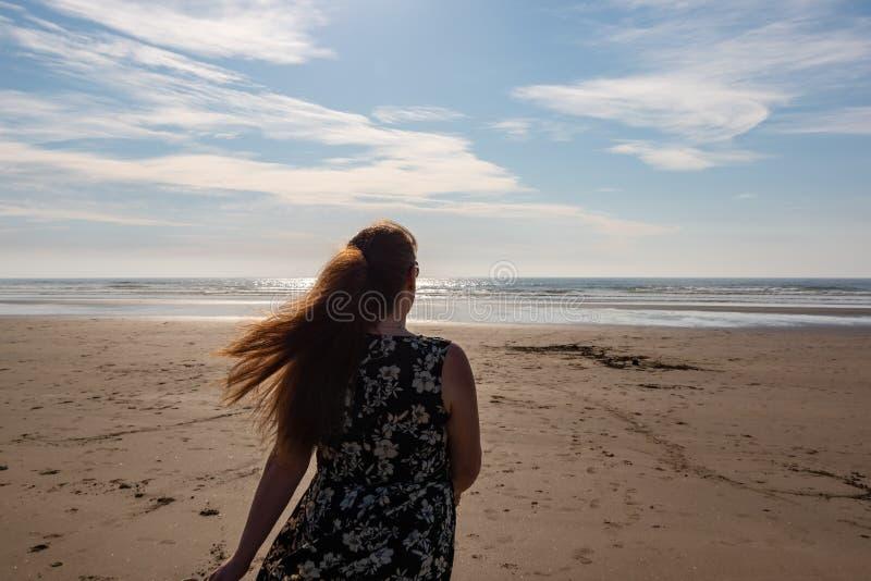 Kvinna som går på stranden till vatten royaltyfri foto
