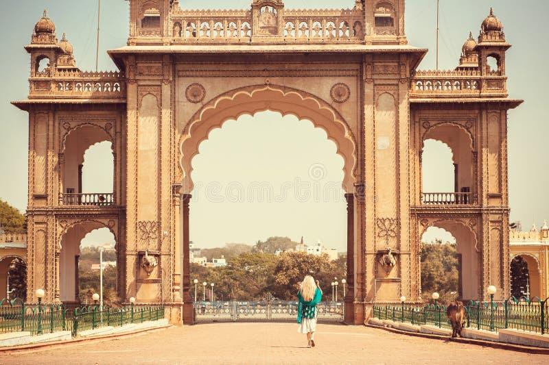 Kvinna som går till den berömda gränsmärket - historiska portar av den kungliga slotten av Mysore i Karnataka, Indien arkivbild