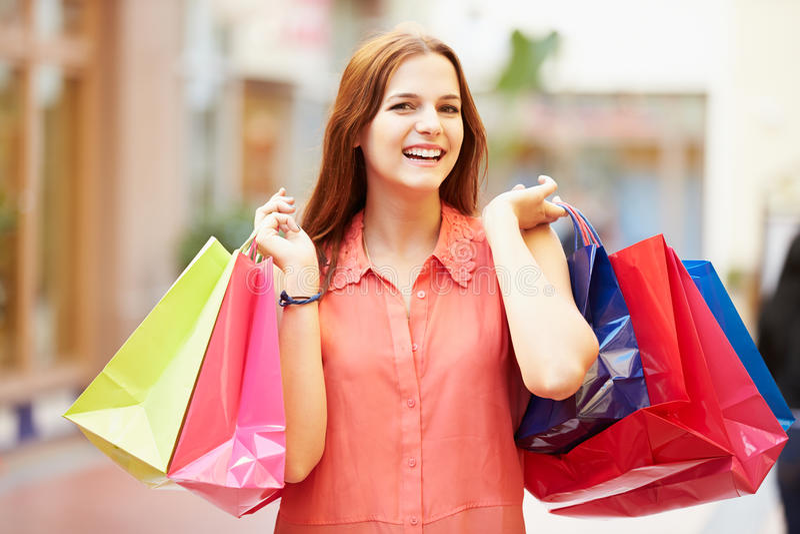 Kvinna som går till och med bärande shoppingpåsar för galleria arkivbild