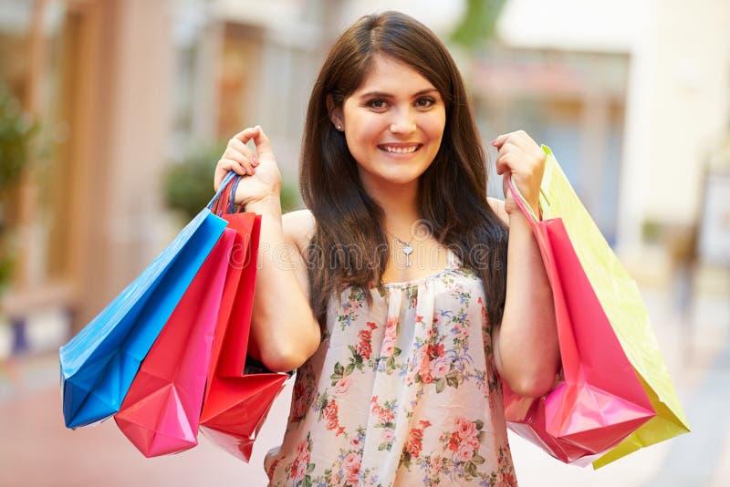 Kvinna som går till och med bärande shoppingpåsar för galleria royaltyfri fotografi
