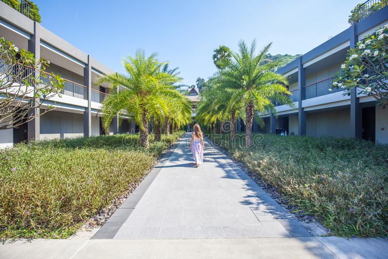 Kvinna som går till och med palmträdgränden arkivfoto