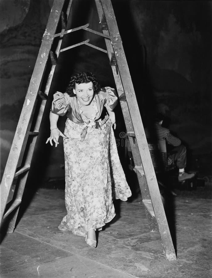 Kvinna som går under en momentstege med henne korsade fingrar (alla visade personer inte är längre uppehälle, och inget gods finn arkivbilder