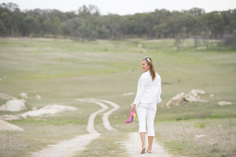 Kvinna som går utomhus- hållande höga häl för kal fot royaltyfri fotografi