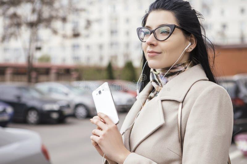 Kvinna som går utomhus på en gata i laget, kallt väder Henne oss arkivfoto