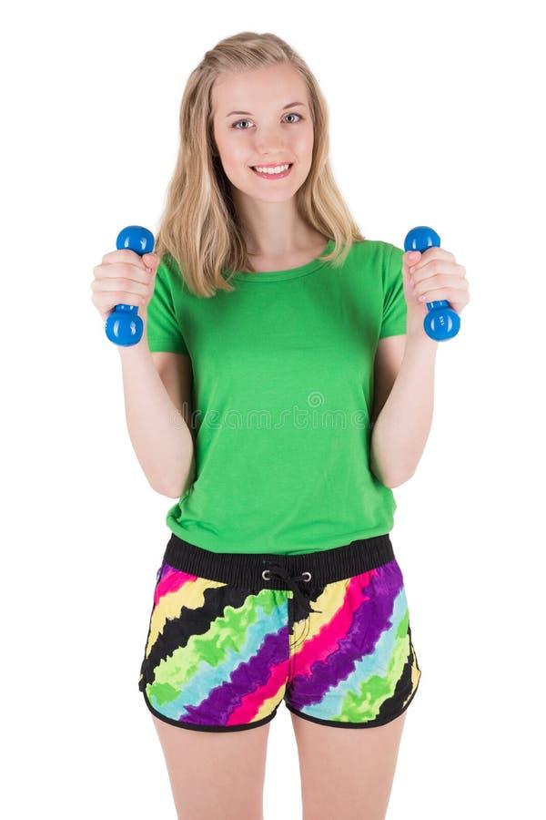 Kvinna som gör övning med blåa hantlar i sportswear fotografering för bildbyråer
