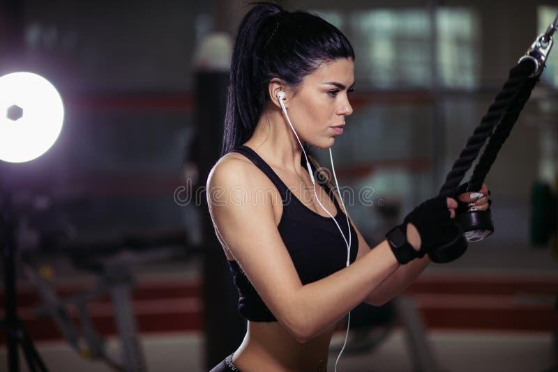 Kvinna som gör övning på övergångsmaskinen i idrottshall royaltyfria foton