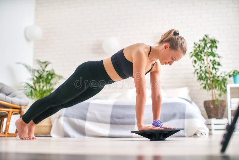 Kvinna som gör övning på en special simulatorstabilisator den blonda idrotts- sportswearen, övade hem förstärker musklerna arkivbilder