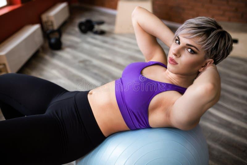 Kvinna som gör övningar med fitball i konditionidrottshallgrupp Kopplande in buk- muskler för kärna Bildbegrepp av sunt royaltyfri foto
