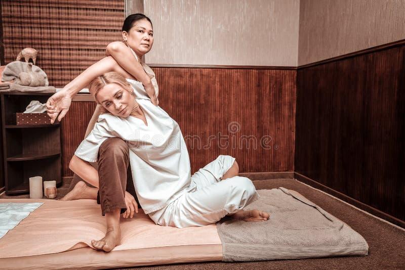 Kvinna som gör övningar under thai massageperiod royaltyfria bilder