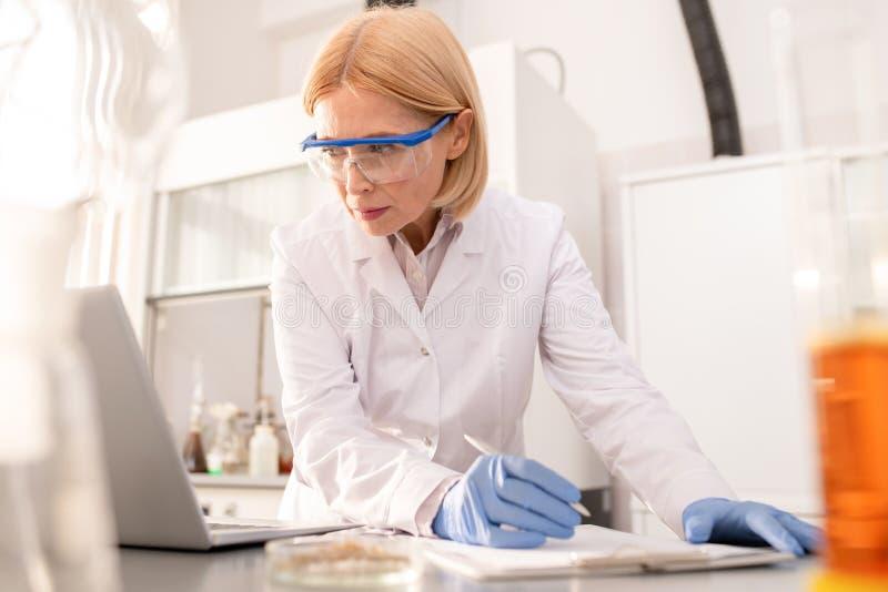 Kvinna som gör anmärkningar om vetenskaplig forskning royaltyfria foton