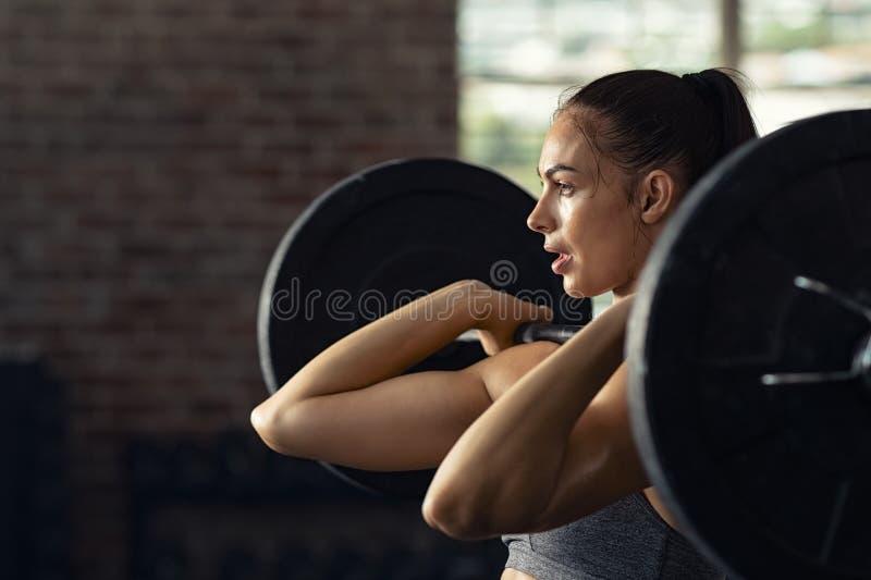 Kvinna som gör att lyfta för vikt på den arga färdiga idrottshallen arkivbild