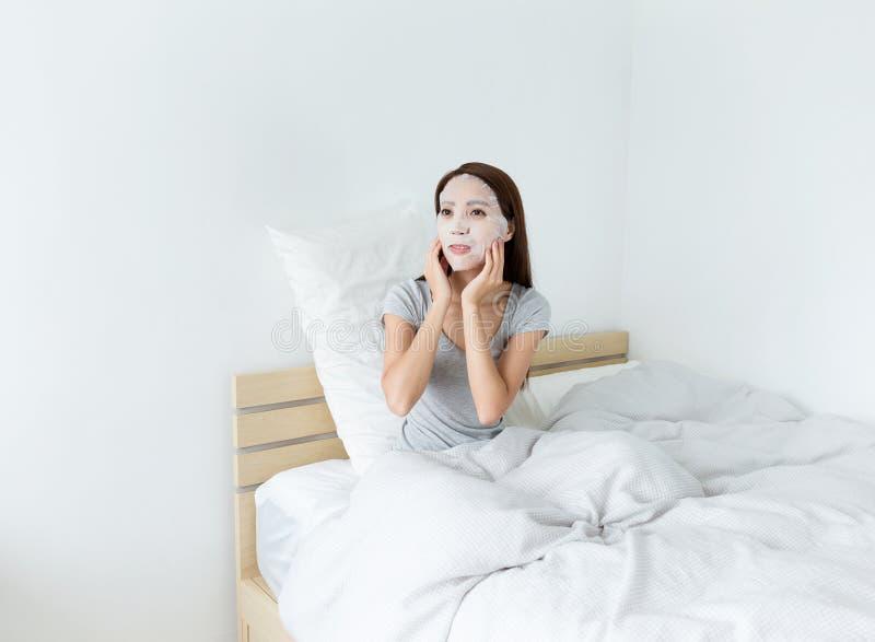 Kvinna som gör den ansikts- maskeringen på säng arkivfoton
