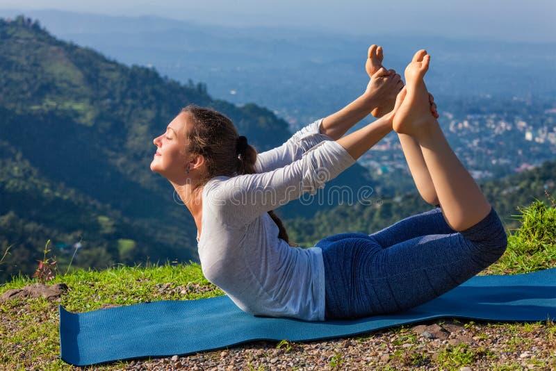 Kvinna som gör den Ashtanga Vinyasa yogaasanaen Dhanurasana - pilbågen poserar fotografering för bildbyråer