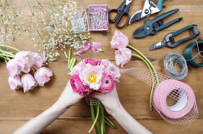 Kvinna som gör den härliga buketten av rosa persisk smörblomma arkivbild