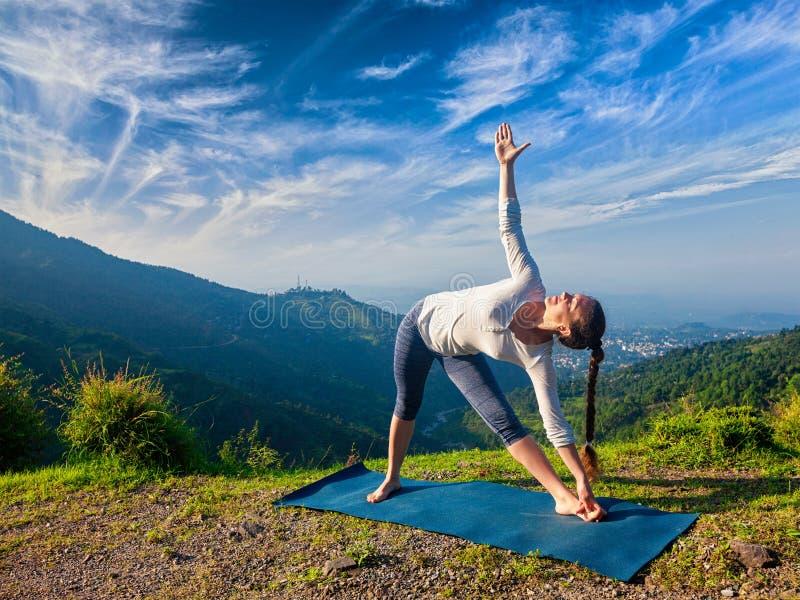 Kvinna som gör den Utthita för Ashtanga Vinyasa yogaasana trikonasanaen fotografering för bildbyråer