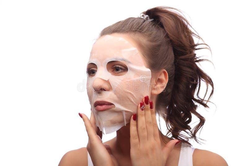 Kvinna som gör det ansikts- maskeringsarket Skönhet och begrepp för hudomsorg Flicka som applicerar den ansikts- maskeringen arkivfoton