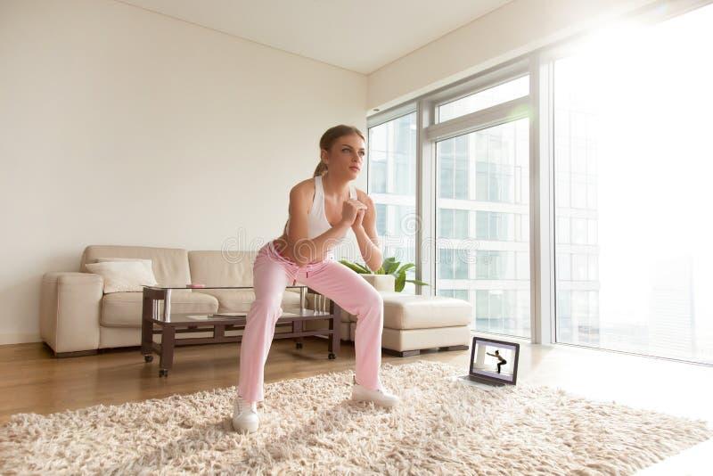 Kvinna som gör djupa squats i vardagsrum hemmastadda arkivbild