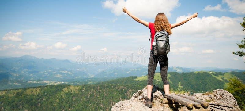 Kvinna som gör en gest framgång med armar, upp når att ha klättrat till maximumet arkivbild