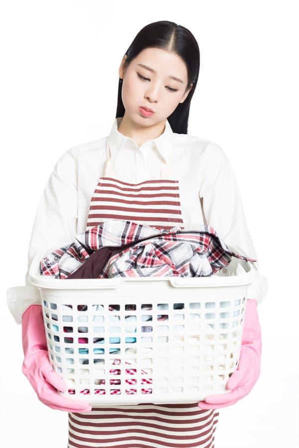 Kvinna som gör en hållande korg för hushållsarbete av tvätterit royaltyfri bild