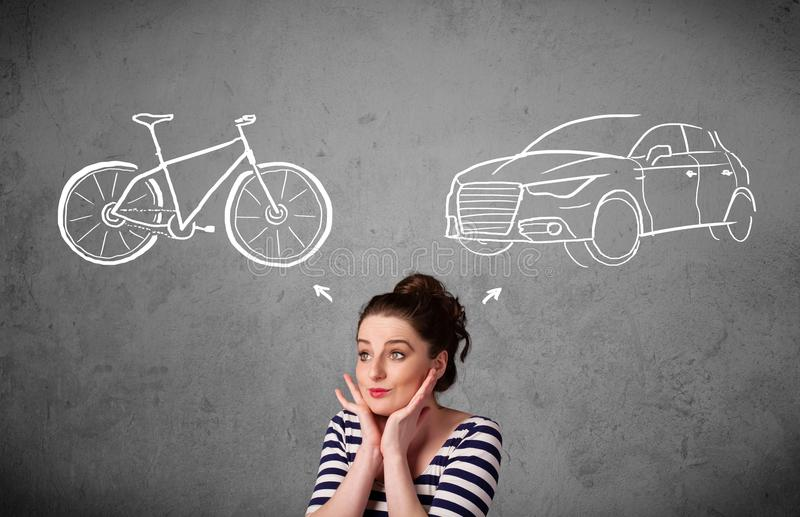 Kvinna som gör ett val mellan cykeln och bilen royaltyfri fotografi