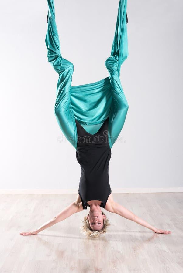 Kvinna som gör flyg- yoga som är uppochnervänd på huvudet royaltyfri foto