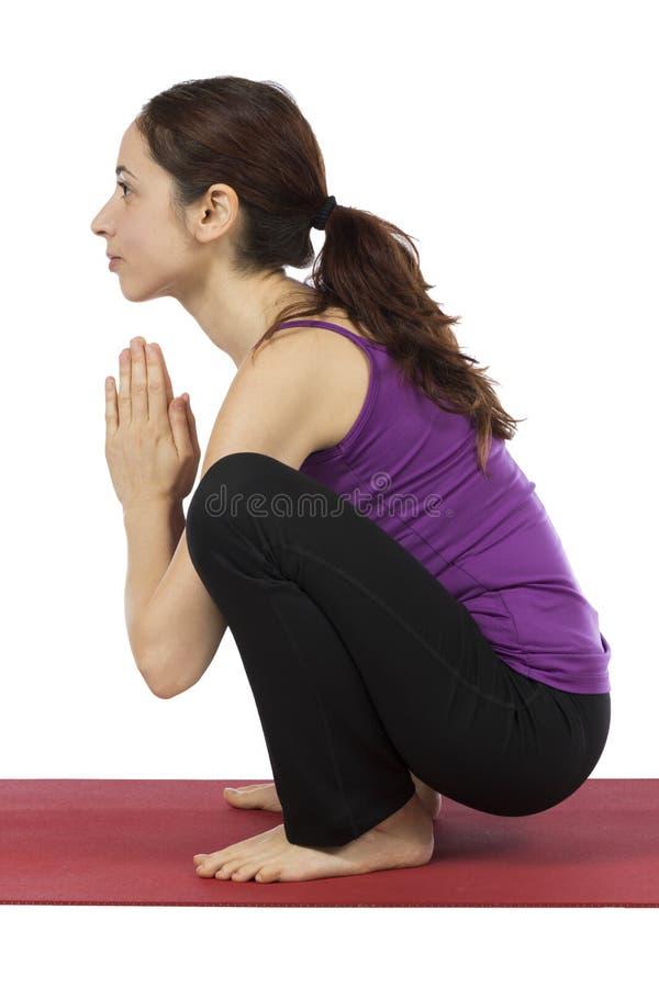 Kvinna som gör Garland Pose i yoga royaltyfri fotografi