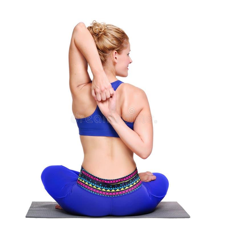 Kvinna som gör Gomukhasana yogaasana arkivfoto