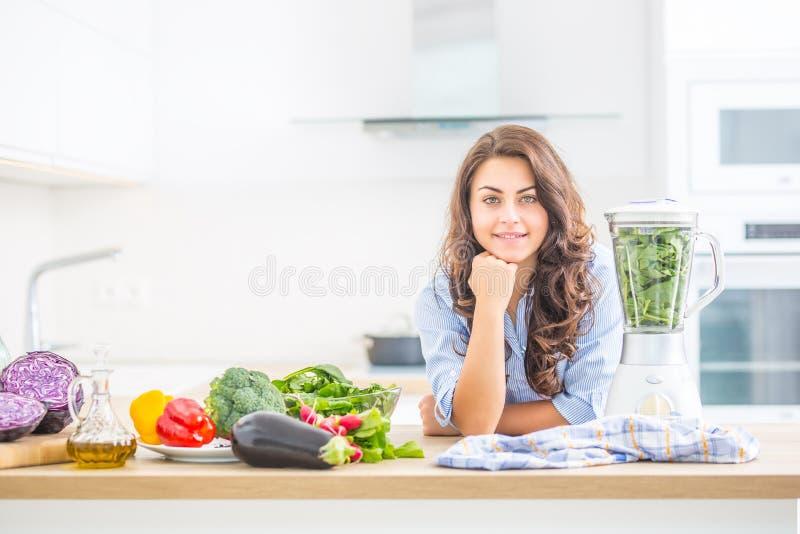 Kvinna som gör grönsaksoppa eller smoothies med blandaren i hennes kök Ung lycklig kvinna som förbereder den sunda drinken med sp arkivfoton