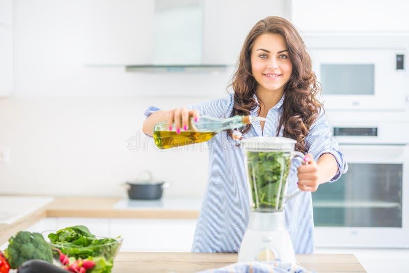 Kvinna som gör grönsaksoppa eller smoothies med blandaren i hennes kök Ung lycklig kvinna som förbereder sund mat eller drinken m royaltyfri fotografi