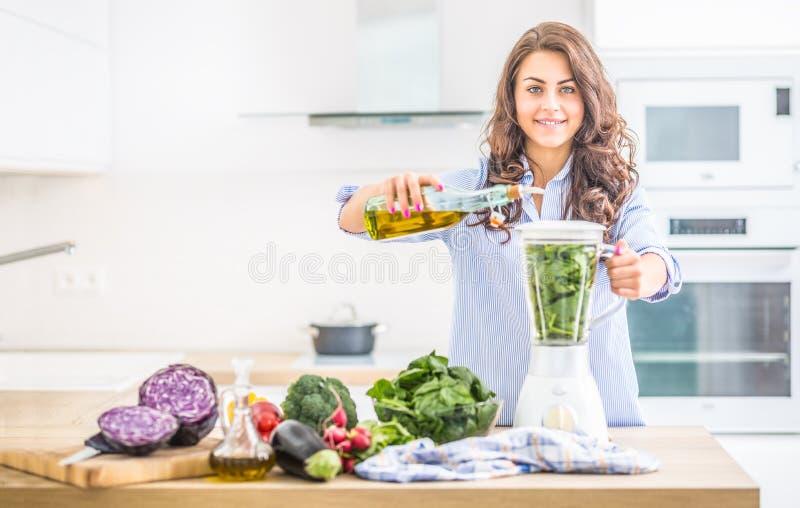 Kvinna som gör grönsaksoppa eller smoothies med blandaren i hennes kök Ung lycklig kvinna som förbereder sund mat eller drinken m fotografering för bildbyråer