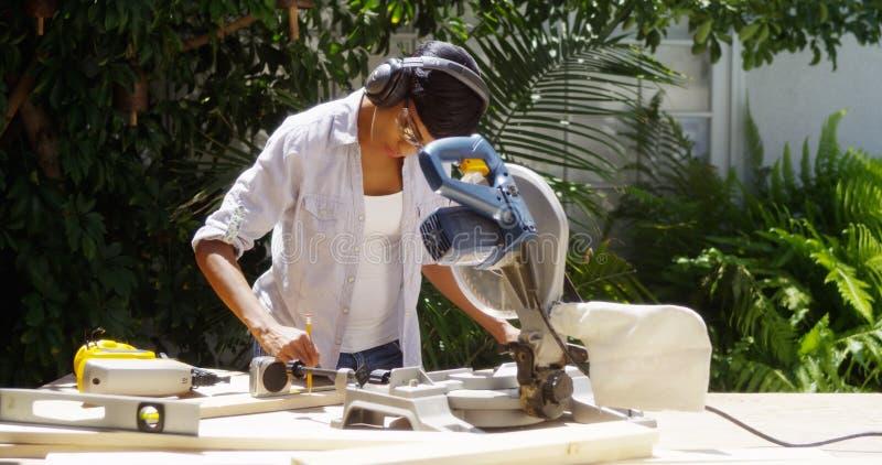 Kvinna som gör hemförbättring som mäter trä royaltyfri bild