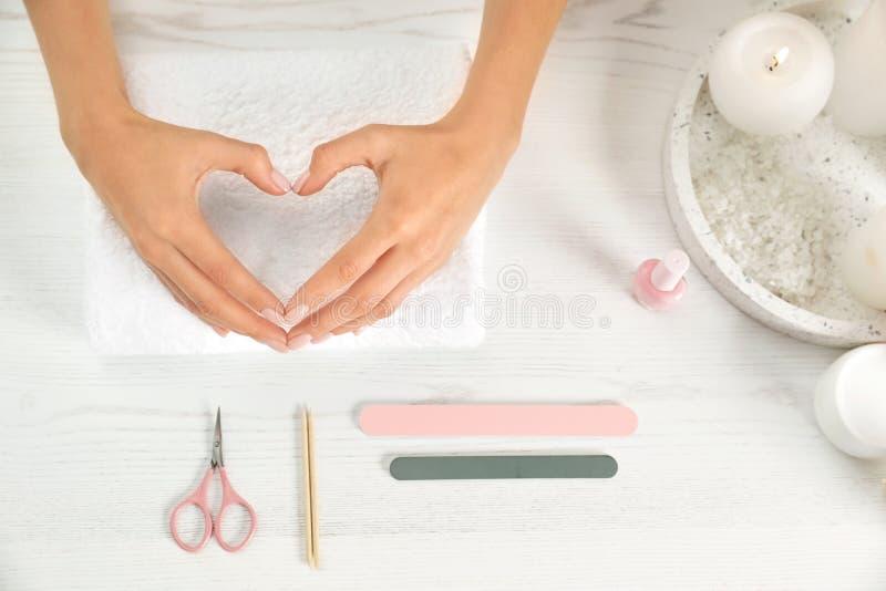 Kvinna som gör hjärta med händer och manikyrhjälpmedel på tabellen, bästa sikt arkivfoto