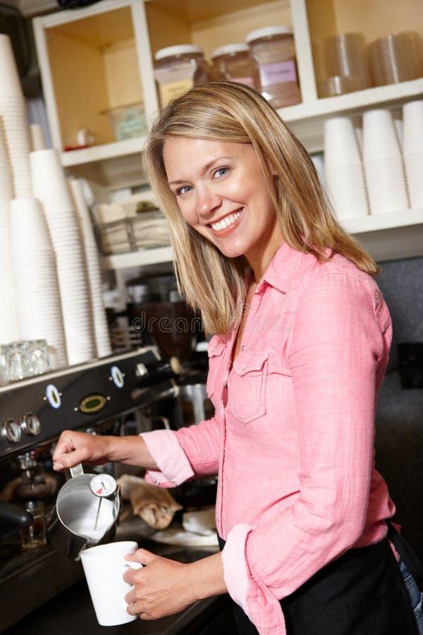Kvinna som gör kaffe i cafe arkivfoto