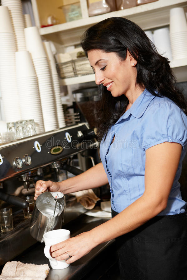 Kvinna som gör kaffe i cafe royaltyfri bild