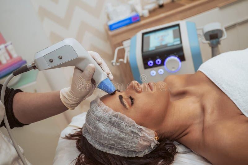 Kvinna som gör kosmetiska behandlingar arkivbilder