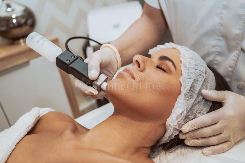 Kvinna som gör kosmetiska behandlingar arkivfoto