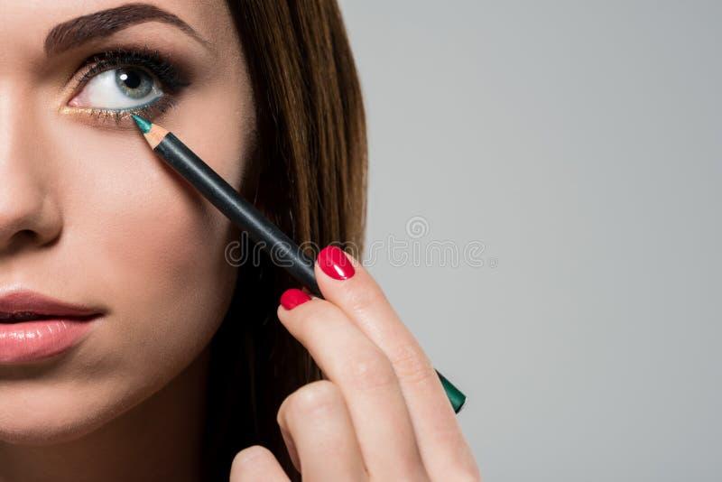 Kvinna som gör makeup med den kosmetiska blyertspennan arkivbilder