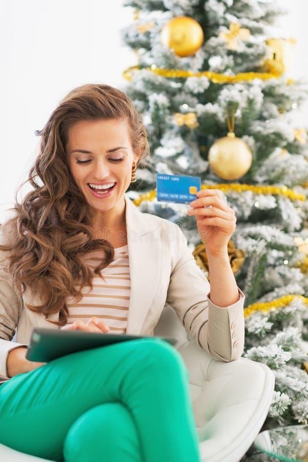 Kvinna som gör online-shopping med minnestavlaPC nära julträd arkivfoton