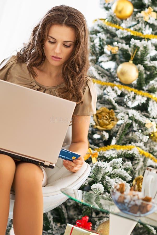 Kvinna som gör online-shopping, medan sitta nära julträd arkivfoton