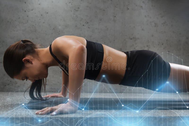 Kvinna som gör push-UPS i idrottshall royaltyfri foto