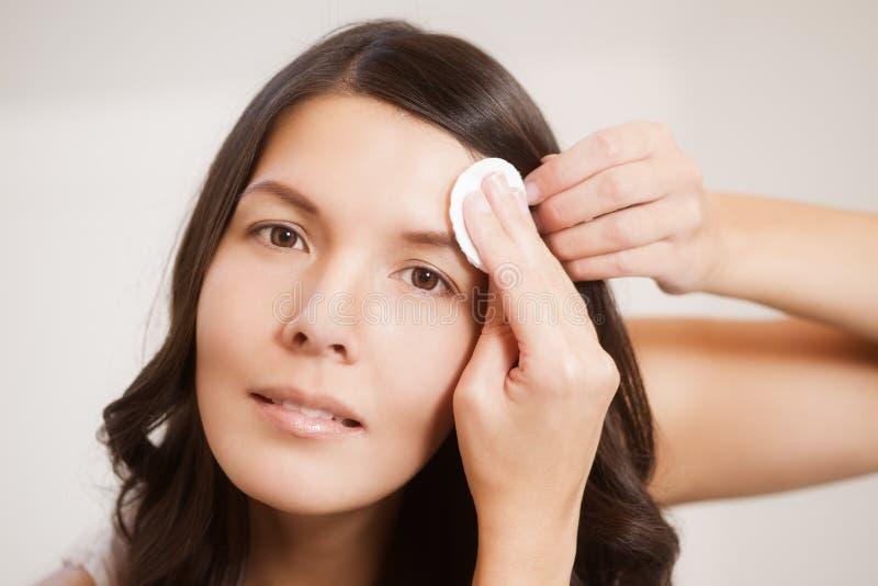 Kvinna som gör ren hennes hud med ett bomullsblock royaltyfri bild