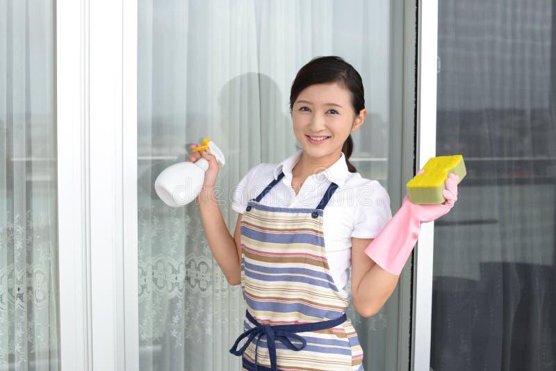Kvinna som gör ren huset arkivbild
