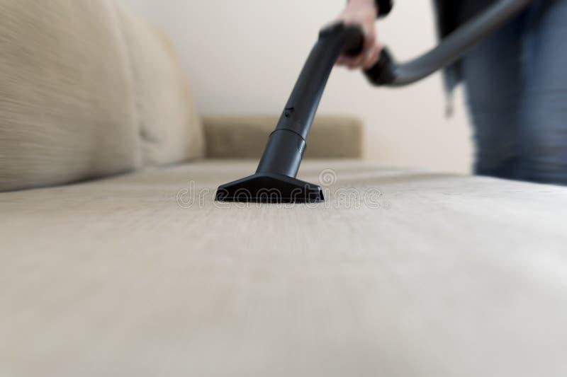 Kvinna som gör ren soffan, soffa med dammsugare arkivbilder