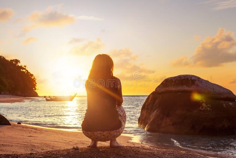 Kvinna som gör satt övning på den sandiga stranden fotografering för bildbyråer