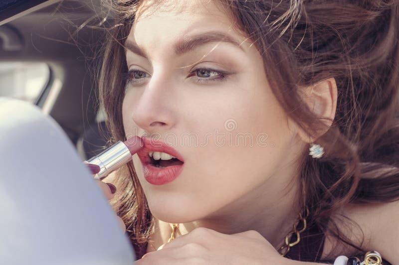 Kvinna som gör smink, medan hon sitter i bilen royaltyfria bilder