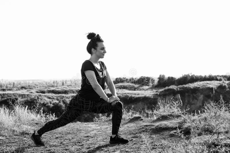 Kvinna som gör sporten som är utomhus- i aftontid som är svartvit arkivfoto