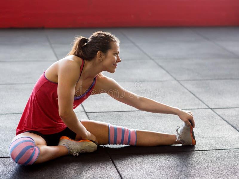 Kvinna som gör sträcka övning i idrottshall arkivbilder